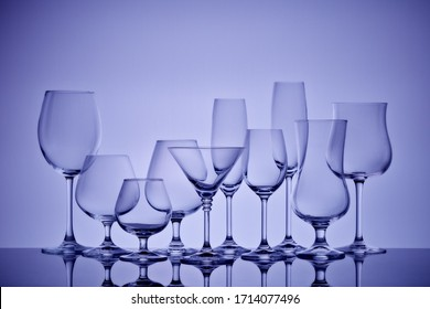 Set of glasses for different alcoholic drinks and cocktails on light gray background. Empty clear glassware.