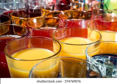 set of glasses with orange and cherry juice on a party