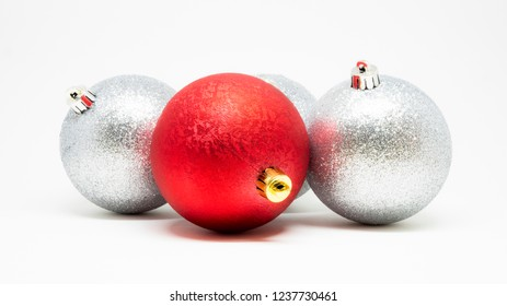 Set of glittering Christmas tree decoration balls isolated on a light background, red one highlighted