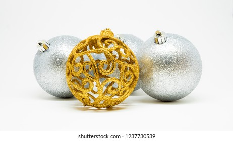 Set of glittering silver Christmas tree decoration balls isolated on a light background, golden one highlighted