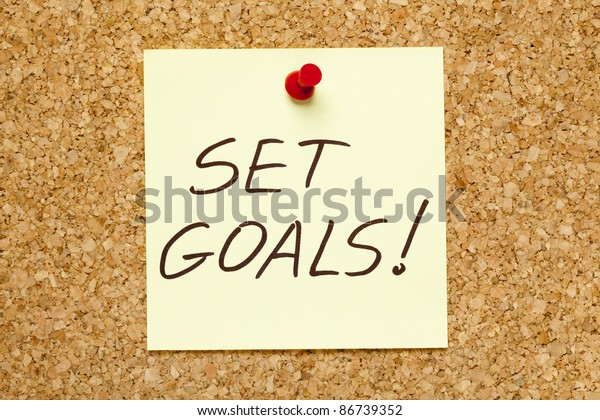 SET GOALS! written on an yellow sticky note on an office cork bulletin board.