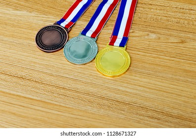 Set of gold silver and bronze award medals  on wooden table.