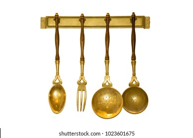 Set of Gold Vintage kitchen utensil hanging on white background.