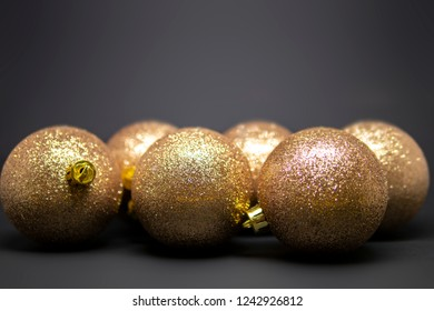 Set of golden Christmas tree decorations isolated on a dark background