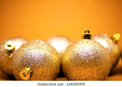 Set of golden Christmas tree decorations on a golden background with space for text