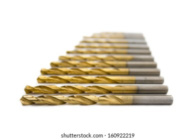 Set of golden drill bits on white background with perspective