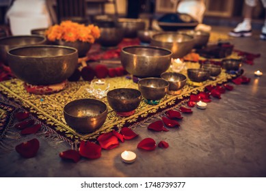 A set of golden tibetian bowls are displayed. They are lying on a yellow carpet with rose petals