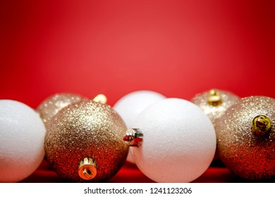 Set of golden and white Christmas tree decorations isolated on a red background