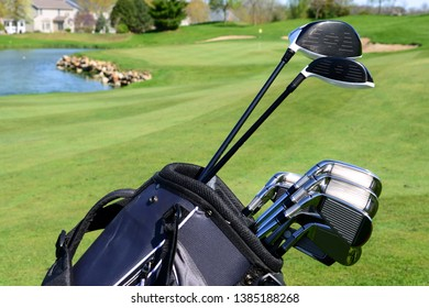 A set of golf clubs standing in a fairway on a scenic golf course with a lake and the green behind them