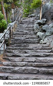 A set of granite stairs with a sturdy metal rail lead down to a viewing area of the Yellowstone canyon.