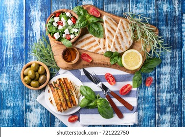 Set of Greek mezze: grilled halloumi cheese, pita bread, grilled bell peppers, green olives and feta with greens decorated with herbs, lemon and olive oil over a blue wooden board. Top View