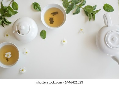 set with green tea, cups and kettle, mint leaves and chamomile flowers, with free space for text, long wide banner