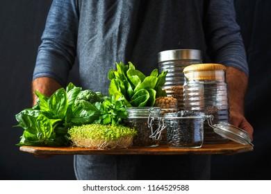 Set green vegetables and various cereals in glass jars in hands man dark background healthy vegan food concept