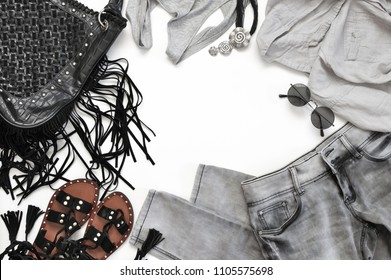 Set of grey and black clothes and accessories on white background. Hippie summer outfit, top view point.