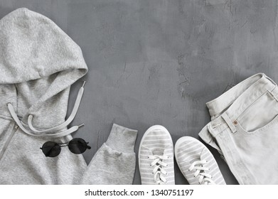 Set of grey casual clothes and accessories on gray background. Top view point, flat lay.