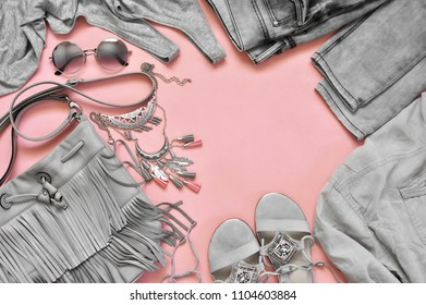 Set of grey clothes and accessories on pink background. Casual summer outfit, top view point, flat lay.