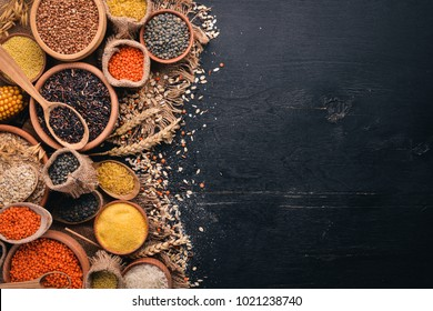 Set of Groats and Grains. Buckwheat, lentils, rice, millet, barley, corn, black rice. On a black background. Top view. Copy space.
