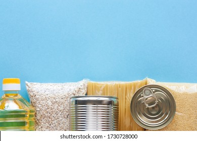 Set of grocery items from pasta, oatmeal, couscous, oil and canned food on blue background top view. Food delivery, donation concept. Food stock for quarantine. Copy space.