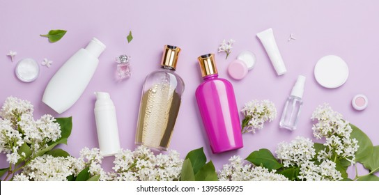 Set of hair care products with white lilac flower (shampoo, balm, mask and hair conditioner etc). Banner with flowers amd cosmetics on purple background. Freshness natural hair care with sping blossom