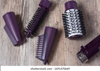 Set of hair dryer attachments on a wooden background. Curling iron, hair straightener. Hot styling, boar bristles, hair care. Beauty salon, styling, haircut. Beauty, fashion, style.