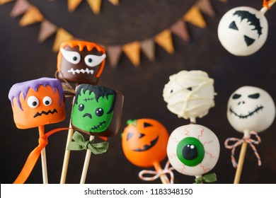 Set of Halloween cake pops and chocolate dipped marshmallow with funny monster faces. Selective focus.