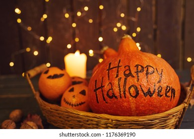 set for Halloween from a pumpkin with an haliday inscription and painted oranges in a wicker basket on a wooden background