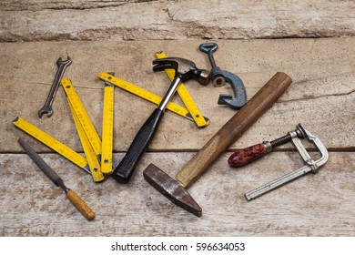 Set of hand working tools over rough wooden background.