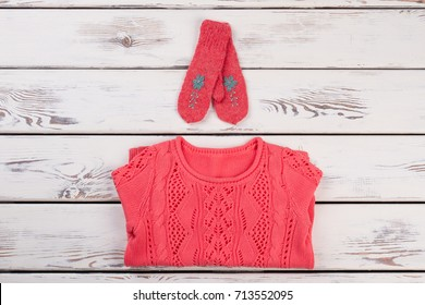 Set of handmade knitted clothes on rustic showcase. Red pullover and mittens, women's fashion wear.