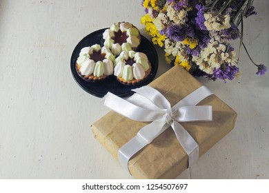 Set of handmade pink zephyr or marshmallow in white box on gray background with bouquet of flowers. Gift concept for a holiday. Marshmallow, Meringue, Zephyr