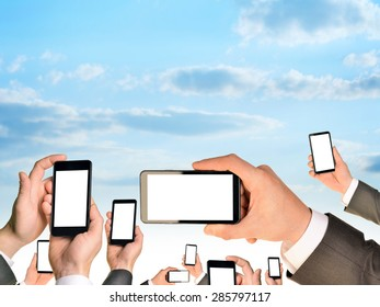 Set of hands holding mobiles on blue sky background
