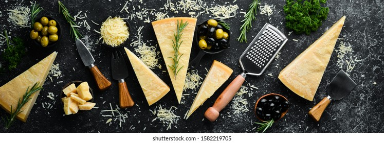Set of hard cheeses with cheese knives on black stone background. Parmesan. Top view. Free space for your text.