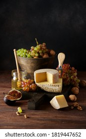 Set of hard cheeses gruyere and manchego on cutting board on dark background. Ripe grapes, walnuts and figs. Still life of seasonal wine snacks