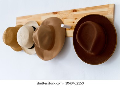 A set of hats hanging on a wooden hanger in a bright cozy bedroom