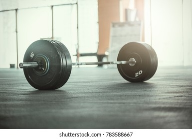 A set of heavy barbells sitting on a gym floor with a sun flare coming through the window