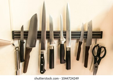 set of high quality kitchen cook knives tools on a magnet board hanging on the wall