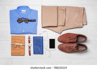 Set of hipster clothes on wooden floor, flat lay