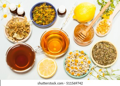 Set of home remedies for fast flu relief and immunity strengthening: herbs, honey, lemon and tea on white background; upper viewpoint