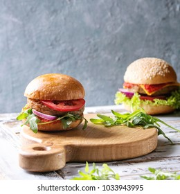 Set of homemade burgers in classic buns with tomato sauce, lettuce, arugula, cheese, onion on wood serving board over white wooden plank table. Rustic style. Homemade fast food. Square image