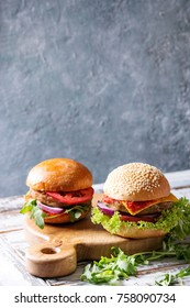 Set of homemade burgers in classic buns with tomato sauce, lettuce, arugula, cheese, onion on wood serving board over white wooden plank table. Rustic style. Homemade fast food.