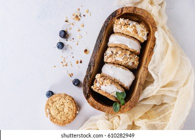 Set of homemade ice cream sandwiches in oat cookies with almond sugar crumbs, blueberries and mint on in olive wooden bowl over gray texture background. Top view with space