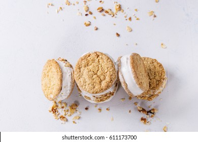 Set of homemade ice cream sandwiches in oat cookies with almond sugar crumbs over gray texture background. Top view with space