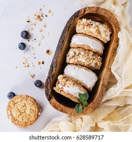 Set of homemade ice cream sandwiches in oat cookies with almond sugar crumbs, blueberries and mint on in olive wooden bowl over gray texture background. Top view with space. Square image