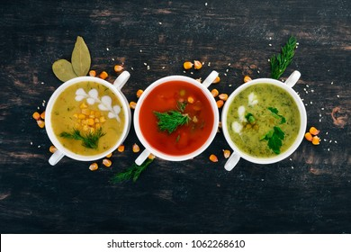 Set of hot, colored vegetable soups. Broccoli soup, corn, tomato soup. Healthy food. On a black wooden background. Copy space.