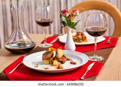 Set of hot meals stands on a table in restaurant. Grilled potato and mushrooms. Romantic dinner with wine.