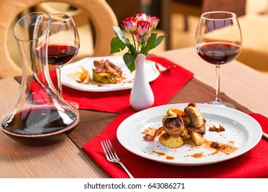 Set of hot meals stands on a table in restaurant. Romantic dinner with wine.