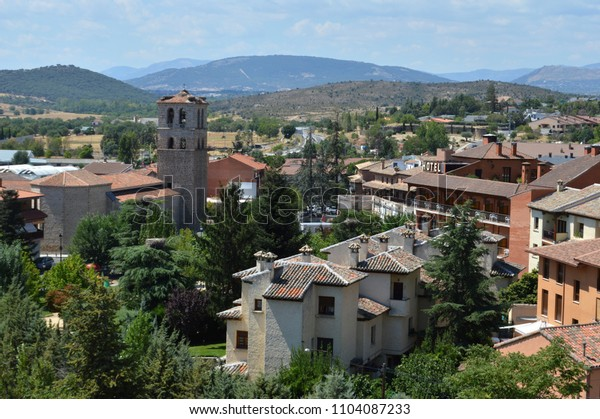 set of house and church of the village of Manzanares el Real with the Sierra de Guadarrama in the background in the province of Madrid. Spain.