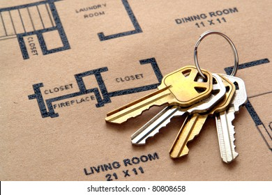 Set of house keys on a key ring over real estate home construction builder architectural floor plan printed on brown recycled paper