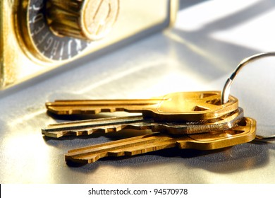 Set of house keys on a ring and real estate brokerage Realtor agent combination safety lock box on shiny reflective surface