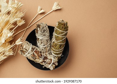 Set of incense for fumigation of premises. Branches of white sage tied in a bunch and dried flowers of Nigella. View from above. Organic holy plant incense from Latin America. Close-up color photo. - Shutterstock ID 1929387170