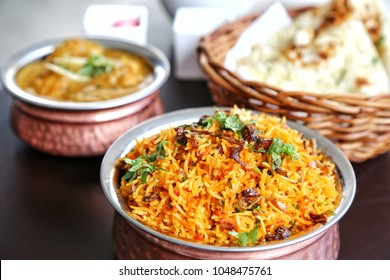 Set of Indian food. Biryani in the front bowl. Curry and naan bread at the back. Indian cuisine consists of a wide variety of regional and traditional cuisines native to the Indian subcontinent.
